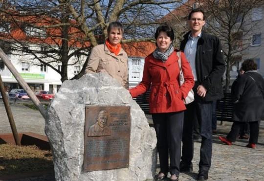 """Ulrike Seifert, Barbara Lochbihler und Oliver Schill vor dem Gedenkstein für Erich Huschka, dem """"Vater von Neugablonz"""" ."""